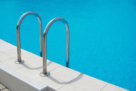 階段と青い水をリラックスできるスイミング プール