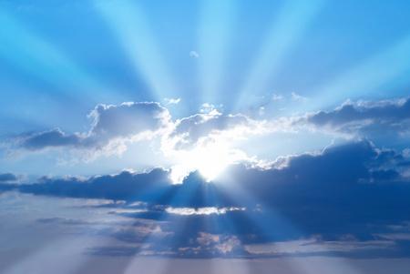 himlen: Vackra blå himmel med solstrålar och moln. Solen strålar.