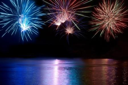 fuegos artificiales: Fireworks colores azules, rojos y blancos por encima del r�o. Celebraci�n de la fiesta.