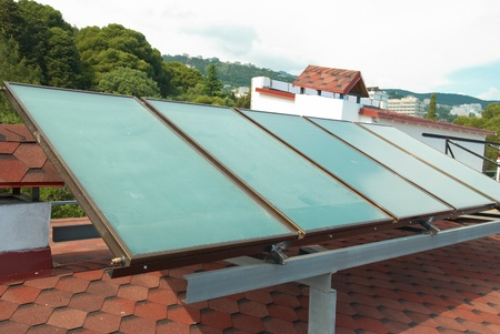 Solar water heating system on the red roof. Gelio panels. photo