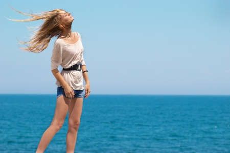 little blonde girl: Beautiful blond girl outdoors against the sea  Stock Photo