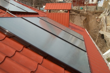 Solar water heating system on the red roof. Gelio panels. Stock Photo - 11154132