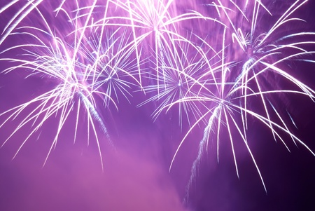 Blue and purple colorful fireworks on the black sky background. Holiday celebration. Stock Photo