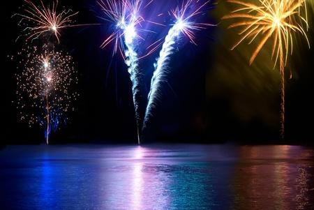 tűzijáték: Kék, piros, fehér és sárga színes tűzijáték a folyó felett. Ünnep ünneplés. Stock fotó