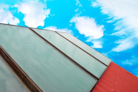 gelio: Solar system on the red house roof with blue sunny sky and clouds.