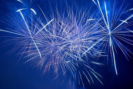 Blue colorful fireworks on the black sky background. Holiday celebration. photo