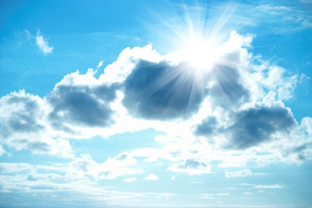Beautiful blue sky with sunbeams and clouds. Sun rays. photo