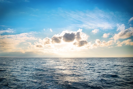 Sea with blue water, sky and clouds. Sunset above seascape photo