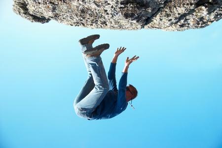 hombre cayendose: Cayendo al hombre de la roca con el fondo azul Foto de archivo