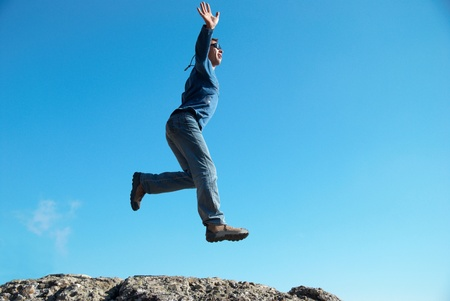 Man jumping on the rocks with landscape background Stock Photo - 12428527