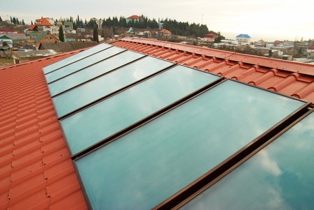 Solar water heating system  geliosystem  on the red house roof  photo