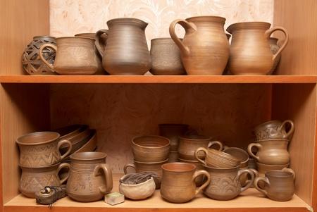 Many handmade old clay pots on the shelf. photo