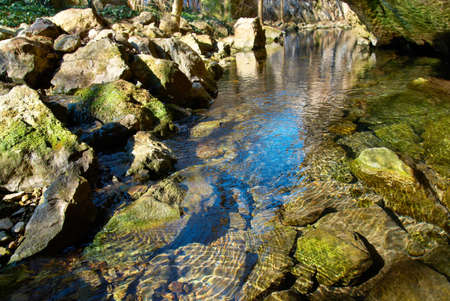 Lake in the forest with rocks and blue sky reflection. photo