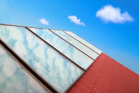 gelio: Solar panels on the red house roof with blue sky and clouds