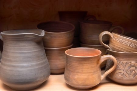 Many handmade old clay pots on the shelf. photo