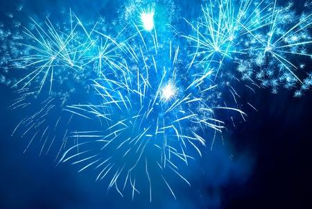blu: Blue colorful fireworks on the black sky background. Holiday celebration.