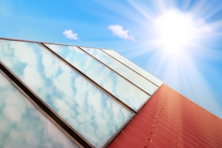 gelio: Solar panels on the red house roof with blue sky, sun and clouds