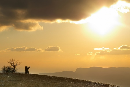 Couple on the hill against sunset. Landscape with clouds and sky. photo