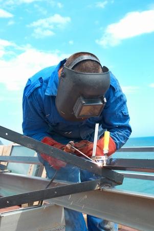 Schweißer bei der Arbeit mit der Fabrik Metallkonstruktion Lizenzfreie Bilder
