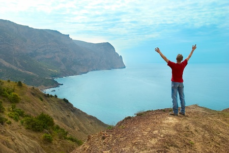 Happy man standing on the cliff with hands up looking at the sea photo