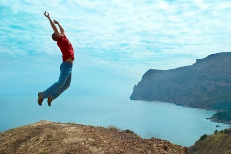 Man jumping cliff against sea and mountain with blue sky Stock Photo - 13549544