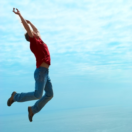 Jumping  man against sea with blue sky and clouds Stock Photo - 13549530
