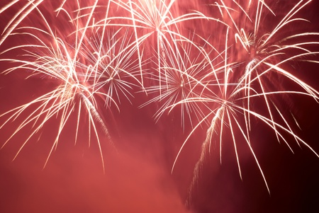 Red colorful fireworks on the black sky background. Holiday celebration. photo
