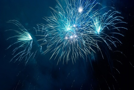 Blue colorful fireworks on the black sky background. Holiday celebration. photo