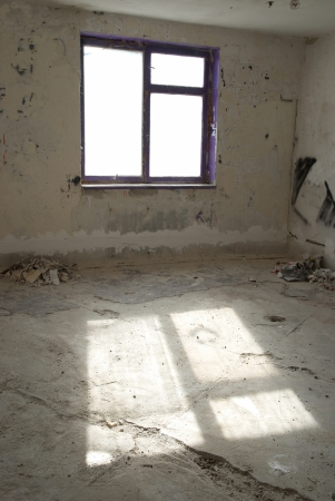 Abandoned empty room with window and light from it photo