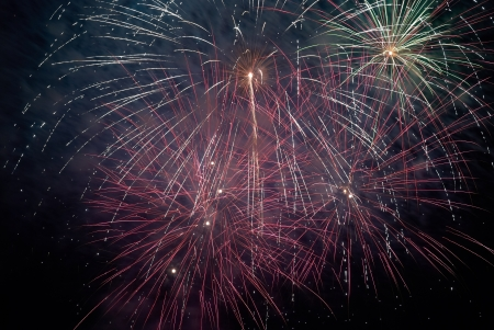 Colorful holiday fireworks on the black sky background. photo