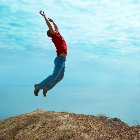 Man jumping cliff against sea and mountain with blue sky Stock Photo - 14645566