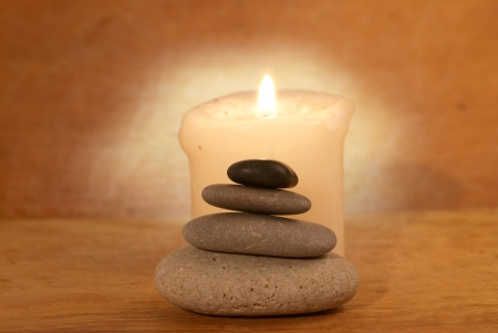 Spa concept with candle, zen stones and wooden background photo
