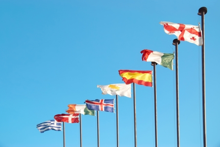 Row of european flags against blue sky background photo