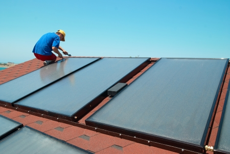 Worker solar water heating panels on the roof. 스톡 콘텐츠