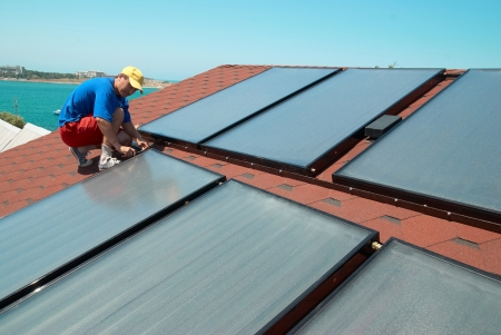 solar panel house: Worker solar water heating panels on the roof. Stock Photo