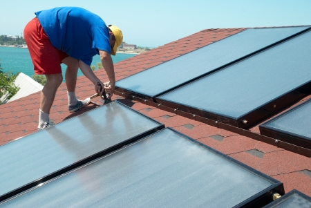 Worker solar water heating panels on the roof. photo