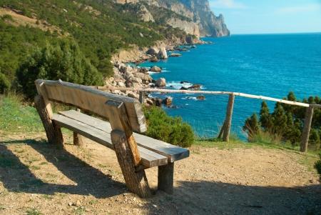 shoreline: Banco de madera hermosa vista sobre el mar. Paisaje entorno verde