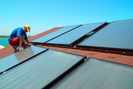 gelio: Worker solar water heating panels on the roof. Stock Photo