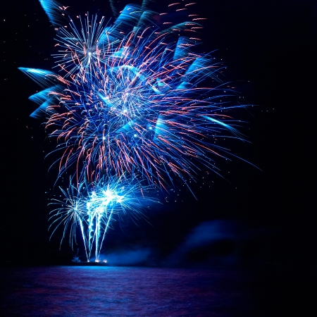 Blue and red colorful holiday fireworks on the black sky background. Stock Photo - 15089029
