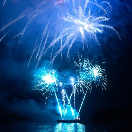 blu sky: Blue colorful holiday fireworks on the black sky background.