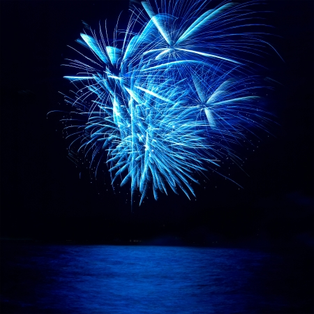Blue colorful holiday fireworks on the black sky background. photo
