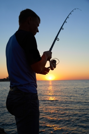 Fisherman fishes on the lake. Silhouette at sunset Stock Photo - 15785270