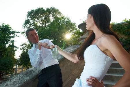 Beautiful wedding couple. Bride pulling groom by the tie photo