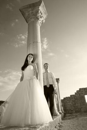 wedding portrait: Beautiful wedding couple- bride and groom near greece column in the ancient city. Black and white, sepia Stock Photo