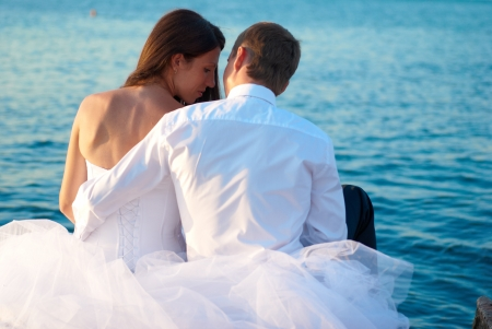 Beautiful wedding couple- bride and groom hugging at the beach. Just married