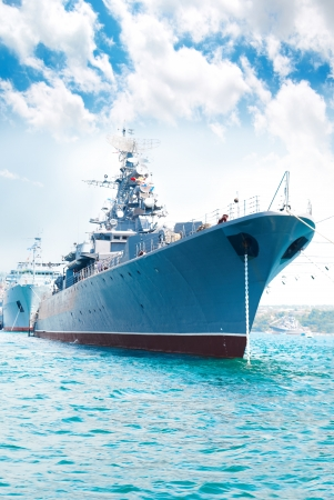warship: Military navy ship in the bay against blue sky Stock Photo