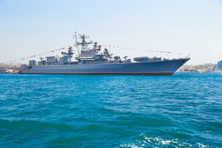 destroyer: Military navy ship in the bay against blue sky Stock Photo
