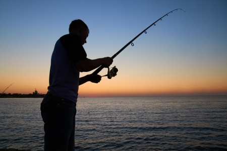 Fisherman fishes on the lake. Silhouette at sunset photo