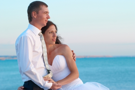 Beautiful wedding couple- bride and groom hugging at the beach. Just married photo