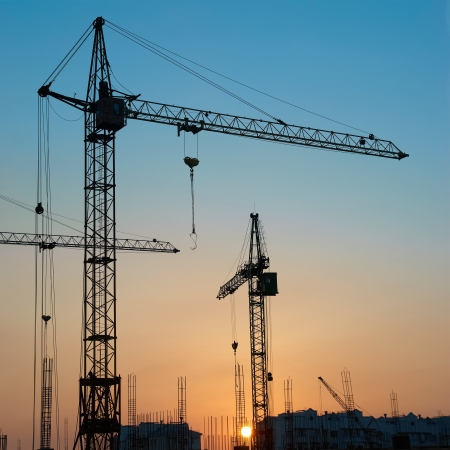 Industrial landscape with silhouettes of cranes on the sunset background
